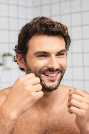 Photo pour Homme souriant tenant fil dentaire et regardant loin dans la salle de bain - image libre de droit