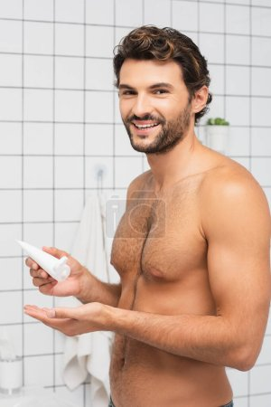 Photo for Smiling shirtless man holding tube with cosmetic cream in bathroom - Royalty Free Image