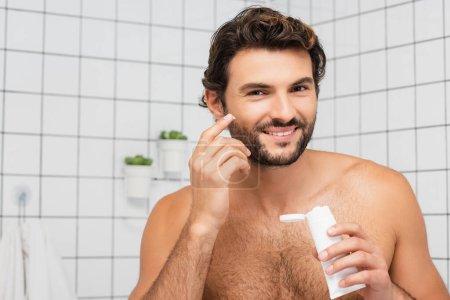 hombre sin camisa sonriendo mientras se aplica crema cosmética en el baño