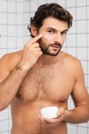 Photo pour Homme torse nu appliquant crème cosmétique sur le visage dans la salle de bain - image libre de droit