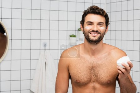 Photo for Smiling shirtless man holding jar with cosmetic cream in bathroom - Royalty Free Image