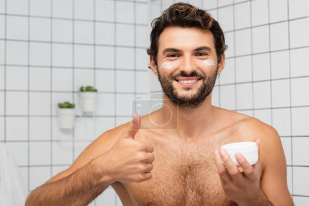 Photo for Smiling shirtless man showing like while holding jar with cosmetic cream in bathroom - Royalty Free Image