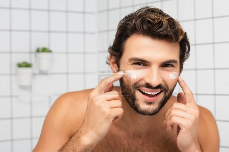 Cheerful shirtless man applying face cream and looking at camera in bathroom