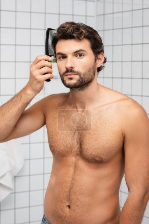 Muscular man combing hair and looking at camera in bathroom