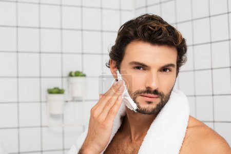 Bearded man with towel applying shaving foam in bathroom