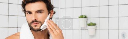 Photo pour Homme barbu appliquant de la mousse à raser dans la salle de bain, bannière - image libre de droit