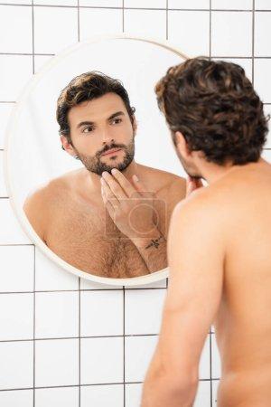 homme torse nu toucher menton tout en regardant miroir dans la salle de bain
