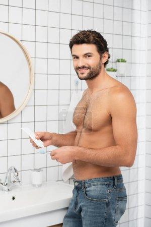 Shirtless man smiling at camera while holding toothpaste and toothbrush in bathroom
