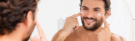 Hombre sonriente aplicando crema cosmética en la cara cerca del espejo en primer plano borroso, pancarta