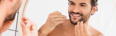 Sonriente hombre sosteniendo hilo dental cerca del espejo en primer plano borroso en el baño, pancarta