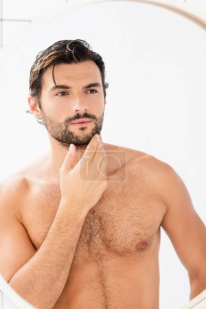 Shirtless man with wet hair touching chin while looking at mirror