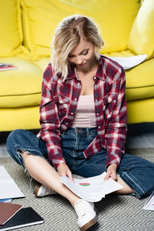 Photo pour Young blonde woman sitting on floor and looking through documents - image libre de droit