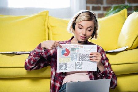 Photo pour Jeune femme blonde ayant webinaire et pointant vers le diagramme - image libre de droit