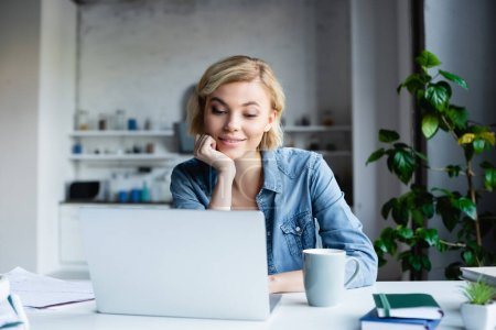 young blonde woman leaning chin on hand and working on laptop