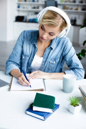 young blonde woman in headphones studying online and making notes