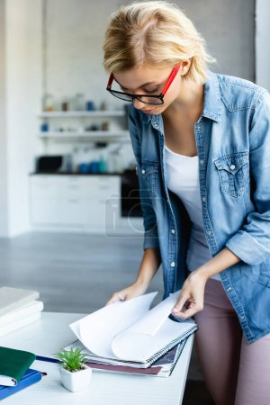 young blonde woman in eyeglasses working from home and turning pages of notebook