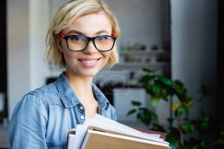 junge blonde Frau mit Brille hält Notizbücher zu Hause