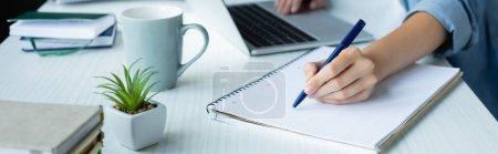 Foto de Cropped view of woman making notes in notebook, horizontal banner - Imagen libre de derechos