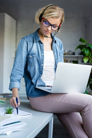 young blonde woman in eyeglasses working from home with laptop and writing notes