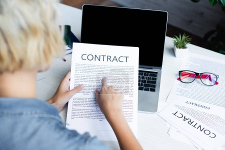 back view of woman pointing with finger at contract
