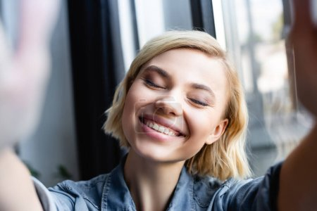 blonde woman smiling with closed eyes