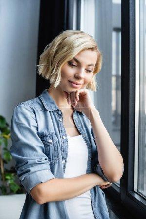 portrait of pensive woman standing near window