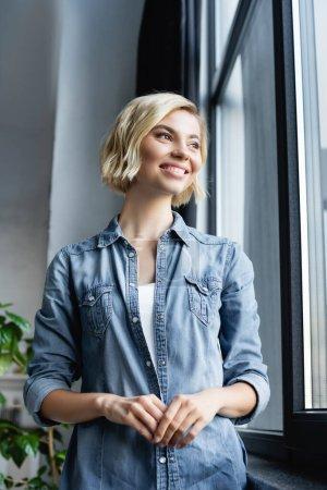 portrait of smiling woman standing near window