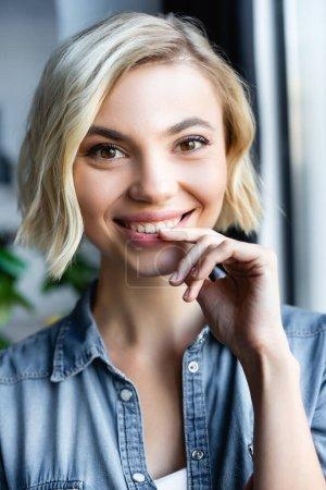 portrait of smiling blonde woman standing near window