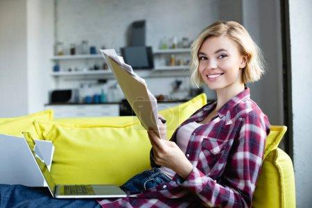 Photo pour Femme blonde en chemise à carreaux travaillant à la maison et regardant à travers les documents - image libre de droit
