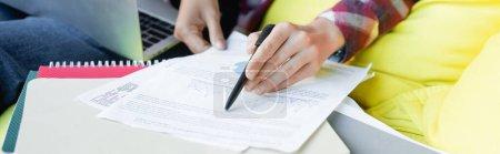 Photo pour Cropped view of woman with pen reading document, banner - image libre de droit