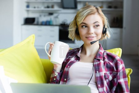young blonde woman in headphones working from home and drinking tea