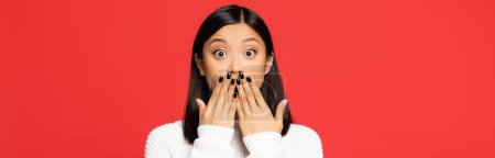 Photo for Shocked asian woman covering mouth with hands isolated on red, banner - Royalty Free Image