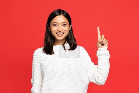 glücklich asiatische Frau im Pullover zeigt mit dem Finger isoliert auf rot