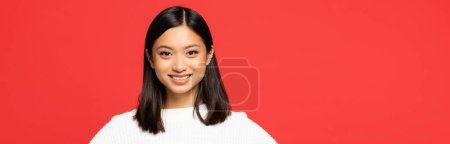 happy and young asian woman in sweater looking at camera isolated on red, banner
