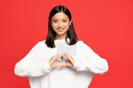 happy and young asian woman showing heart sign with hands isolated on red