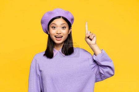 Photo pour Heureux asiatique femme dans béret pointant avec doigt isolé sur jaune - image libre de droit