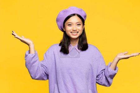 Photo pour Heureux asiatique femme dans béret pointant avec mains isolé sur jaune - image libre de droit