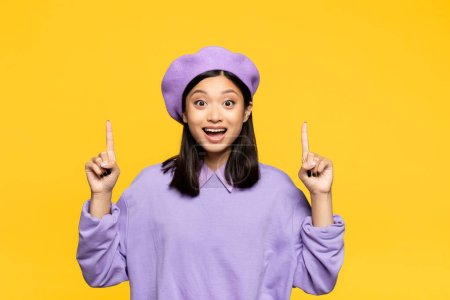 happy asian woman in beret pointing with fingers isolated on yellow
