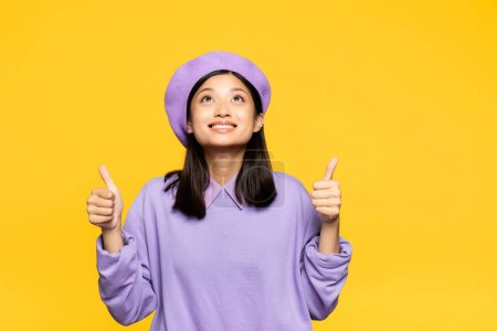 happy asian woman in beret showing thumbs up and looking up isolated on yellow