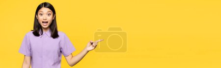 excited asian woman with open mouth pointing with finger isolated on yellow, banner