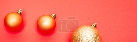 top view of shiny baubles on red background, banner