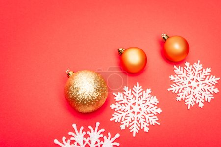 Photo for Top view of snowflakes, baubles on red background - Royalty Free Image
