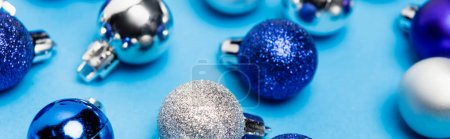 shiny Christmas baubles on blue background, banner