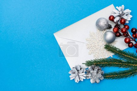Photo for Top view of snowflake, silver baubles, berries, spruce and envelope on blue background - Royalty Free Image
