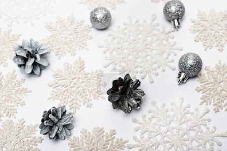 Photo for Top view of snowflakes, silver baubles and cones on white background - Royalty Free Image