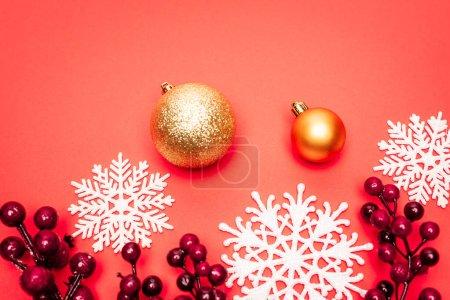 Photo pour Vue de dessus des boules, flocons de neige et baies sur fond rouge - image libre de droit