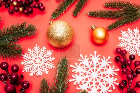 top view of spruce, baubles, snowflakes and berries on red background