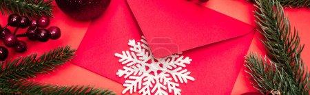 Photo pour Vue du dessus de la décoration de Noël et enveloppe sur fond rouge, bannière - image libre de droit