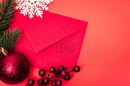 Photo for Top view of Christmas decoration and envelope on red background - Royalty Free Image