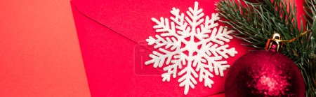 top view of Christmas decoration and envelope on red background, banner